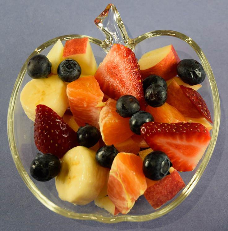 healthy fruit salad in a glass dish shaped like an apple