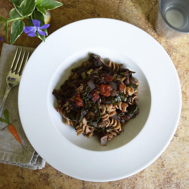 one-bowl pasta meal with tomato sauce, kale, raisins, and walnuts