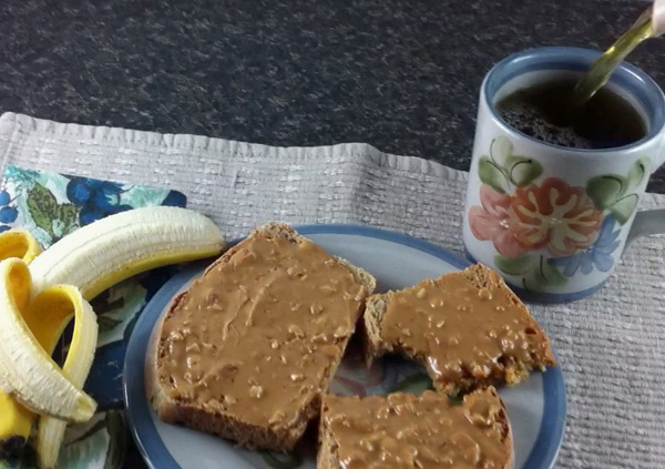 breakfast with peanut butter on toast, banana, and tea