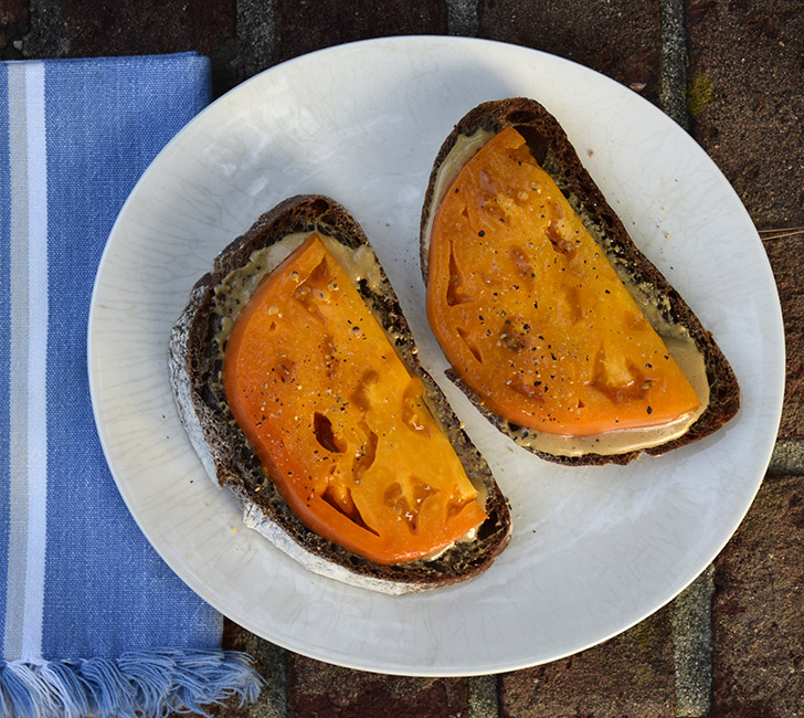tomato tahini toast with yellow tomato