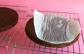 chocolate cake on a cooling rack with parchment partially pulled off
