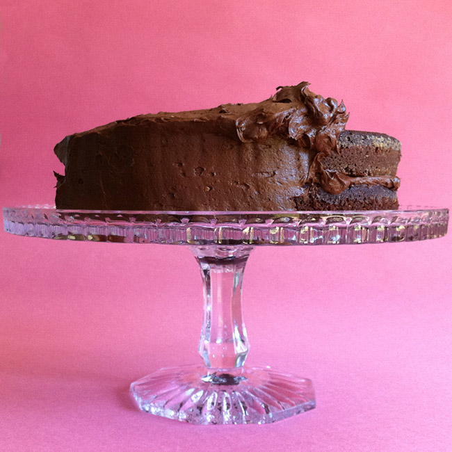 Chocolate Celebration Cake partly frosted on a crystal stand