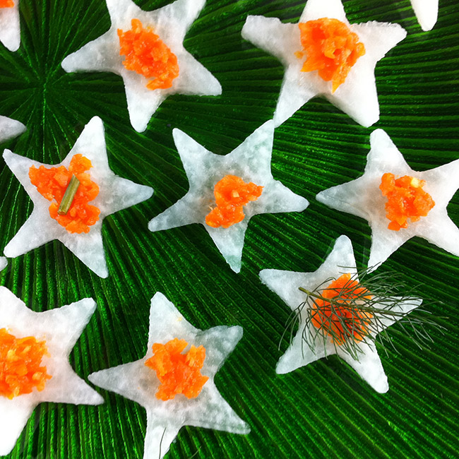 jicama stars topped with ginger and carrot puree on a green plate