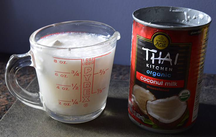 1 cup coconut milk with coconut cream floating in it like an iceberg next to a can of full-fat organic coconut milk