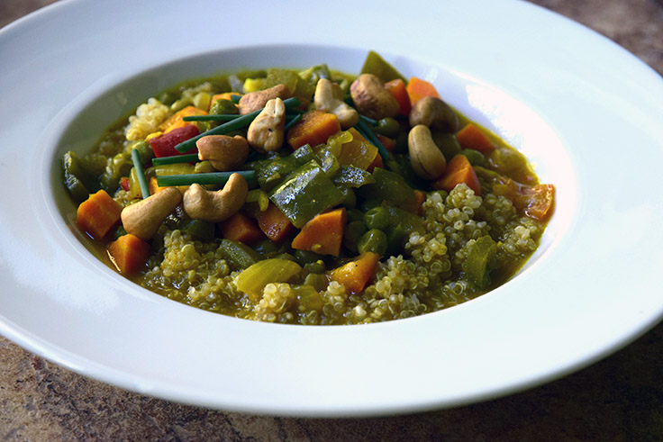 coconut vegetable curry topped with salted cashews and chives