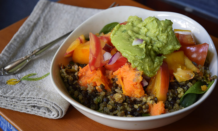 meal with black beluga lentils, quinoa, sweet potato, veggies, and guacamole on a bed of spinach.