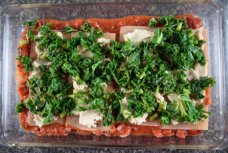 assembling strata in a casserole dish with layers of noodles, tomato sauce, cashew filling, and kale