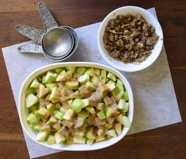 Granny Smith apples cut up in a baking pan and sprinkled with a sugar mixture next to a bowl of crumble topping