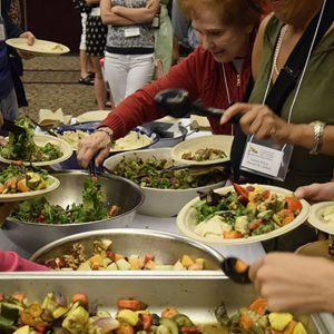 People filling plates at plant-rich buffet