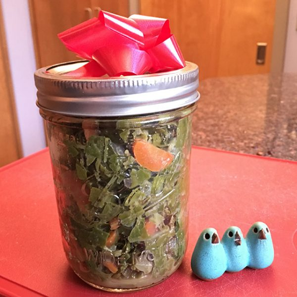 collards with carrots in a mason jar with a red gift bow, three blue pottery birds
