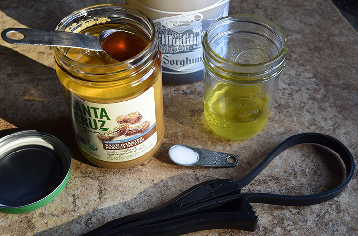adding sorghum to natural peanut butter, with salt for flavor and strap wrench to open jar