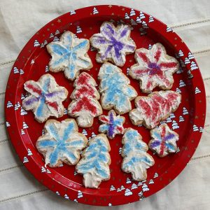 Vegan rolled cookies frosted and decorated on a Christmas plate