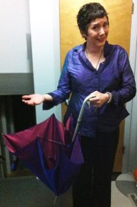 Linda Watson drenched with rain holding an inside-out umbrella