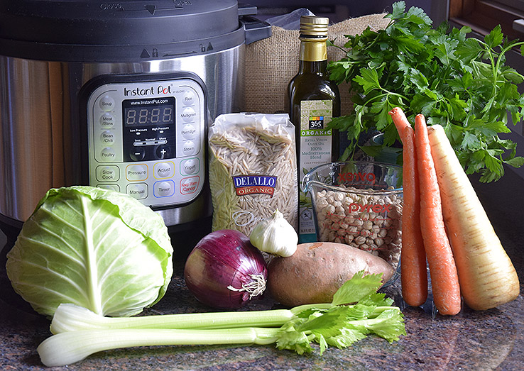vegan ingredients for cold-fighting soup with Instant Pot: cabbage, celery, red onion, chickpeas, sweet potato, carrots, organic whole-wheat noodles, olive oil, garlic, chickpeas, parsley