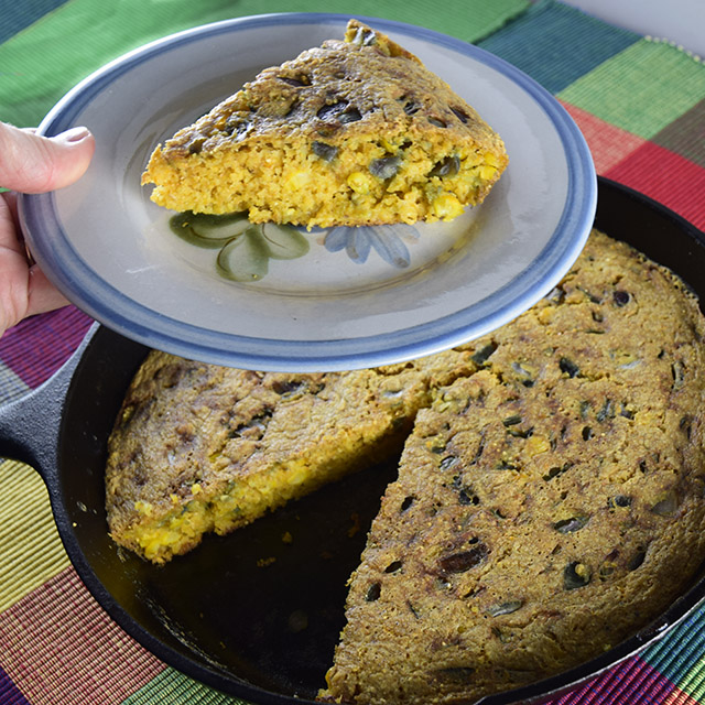 slice of Corny Vegan Cornbread above a skillet of cornbread
