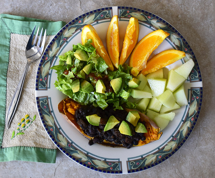 plate with baked sweet potato, black beans, and avocado, green salad, and cut up orange and honeydew melon