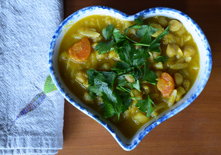 Chickpea and vegetable soup in a heart-shaped bowl with a cloth napkin.