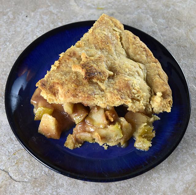 Slice of Vegan Apple Pie on a blue plate