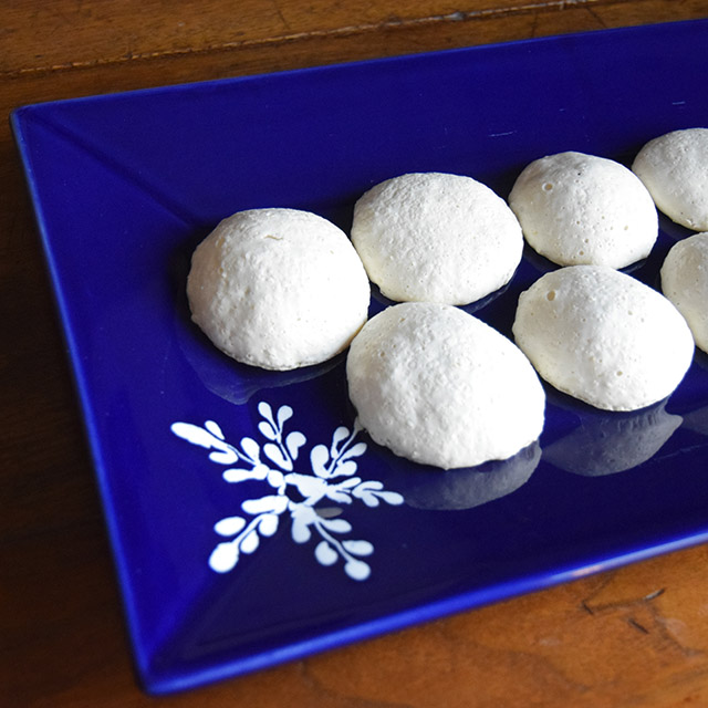 organic aquafaba lemon meringues on a blue plate