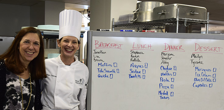 Caralyn House and Heather Therien in Wake Tech teaching kitchen with menu whiteboard