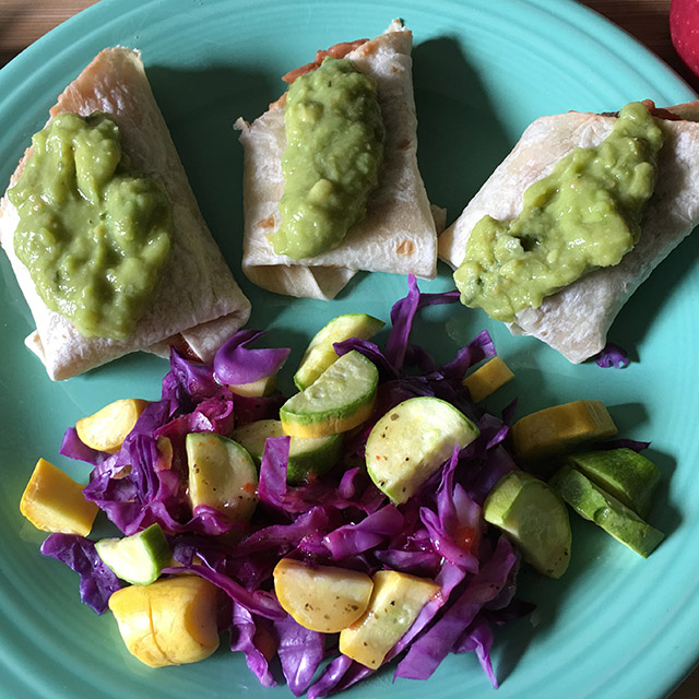 Yellow and green squash with purple cabbage and bean burritos with guacamole.