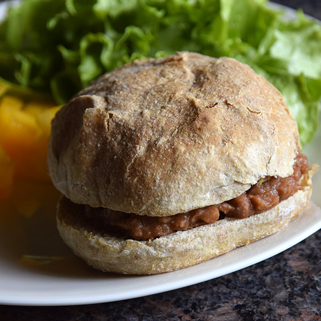 sloppy pinto sandwich on bun with lettuce and melon