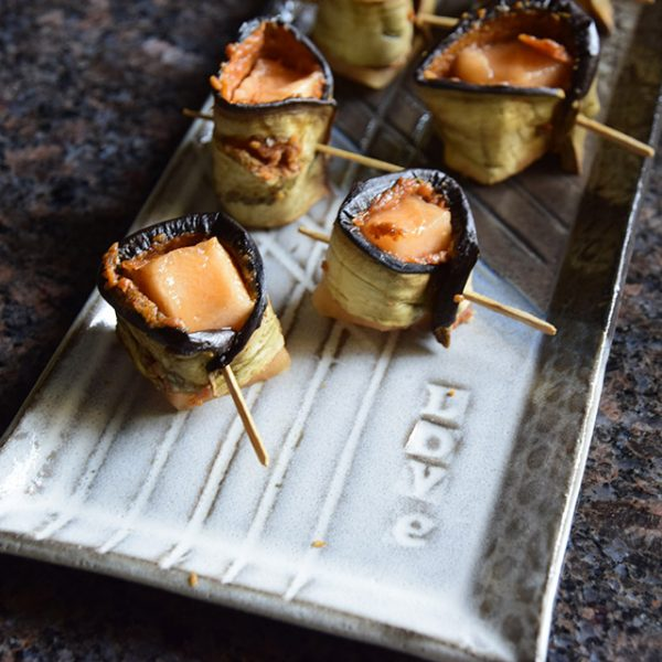 "Spicy eggplant-wrapped melon bites on a handmade tray that says ""love"""