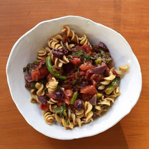 Summer pasta with olives and vegetables in hand-made bowl