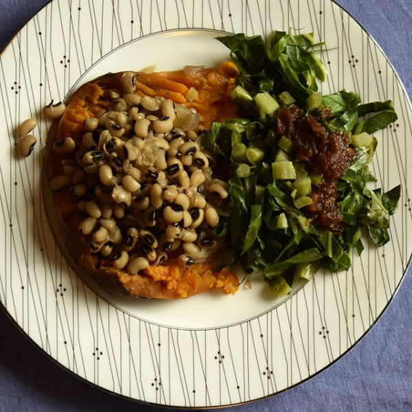 black-eyed peas on a sweet potato with collards and salsa