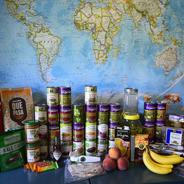 cans and boxes of food plus fresh produce in front of a world map