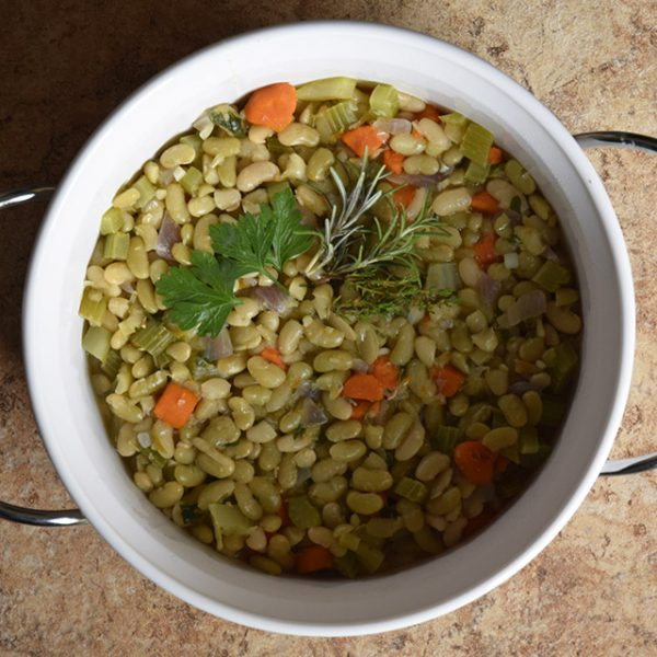 bowl of flageolet beans with carrots and garnish of parsley, rosemary, and thyme