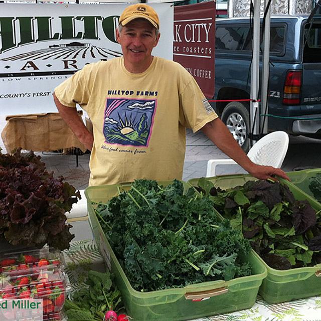 Farmer from Hilltop Farms at farmers' market stand with lettuce and strawberries