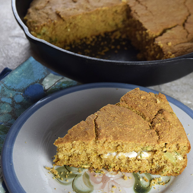 slice of Tawny Cornbread with buttery spread next to cast-iron skillet of cornbread