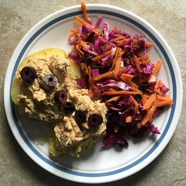 Carrot and Red Cabbage Slaw with a baked potato topped with hummus and olives