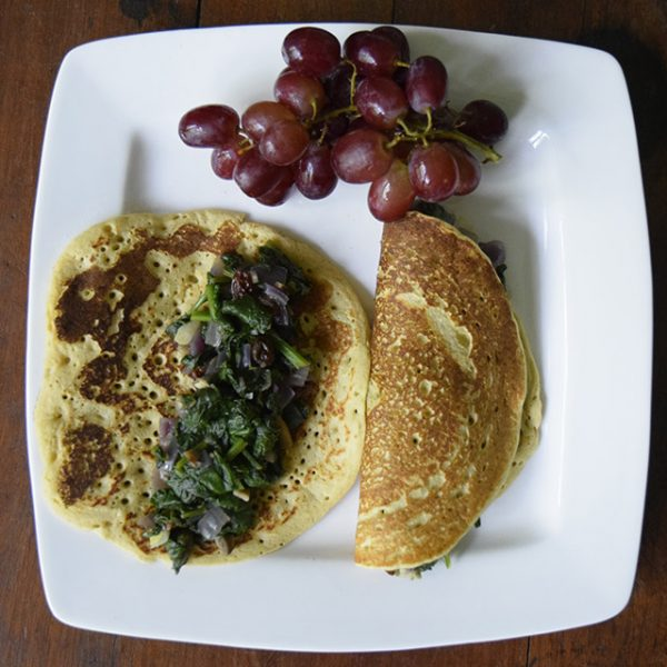 Chickpea pancakes stuffed with spinach and mushrooms, grapes