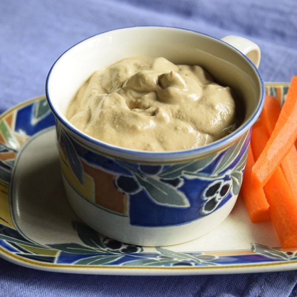 Rich Mushroom Sauce in a cup with carrot sticks on the side