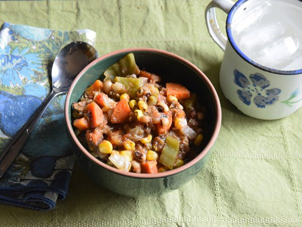 Black-Eyed Pea Stew in a bowl, with a mug of water and a spoon on a cloth napkin.