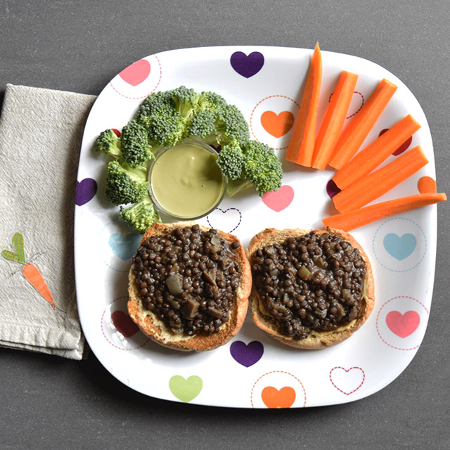 Open-face buns with black lentils, plus broccoli, dipping sauce, and carrots on a heart plate