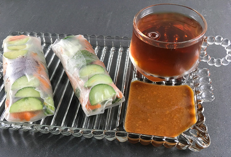 two summer rolls with dipping sauce and a cup of tea on a vintage glass snack set