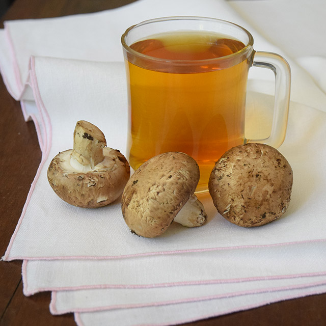 raw mushrooms with a mug of green tea