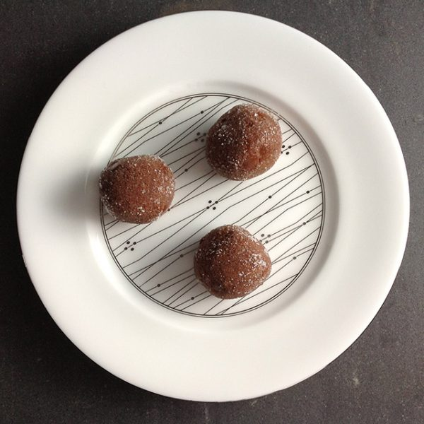 cocoa peanut-butter truffles on a white and silver plate
