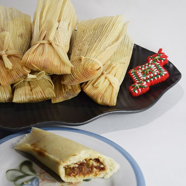 unwrapped tamale with platter of wrapped tamales