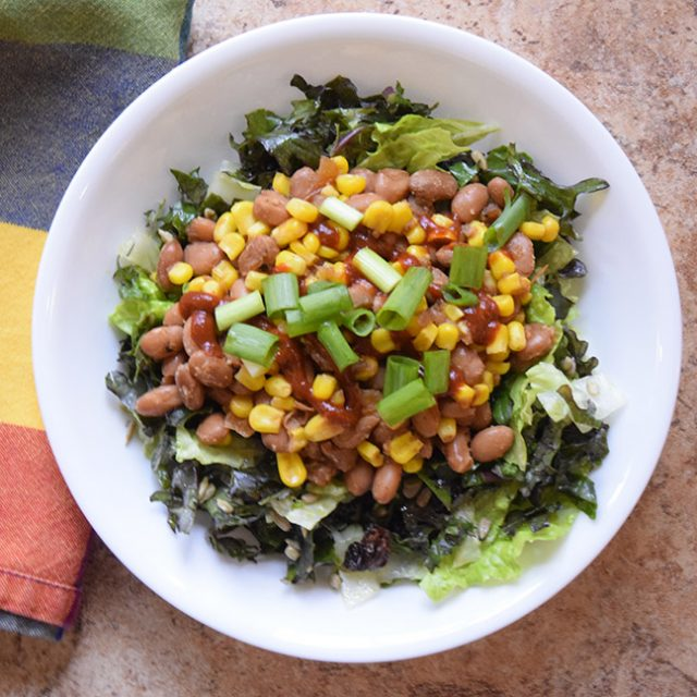 warm bean and corn salad on chopped kale and lettuce in a bowl