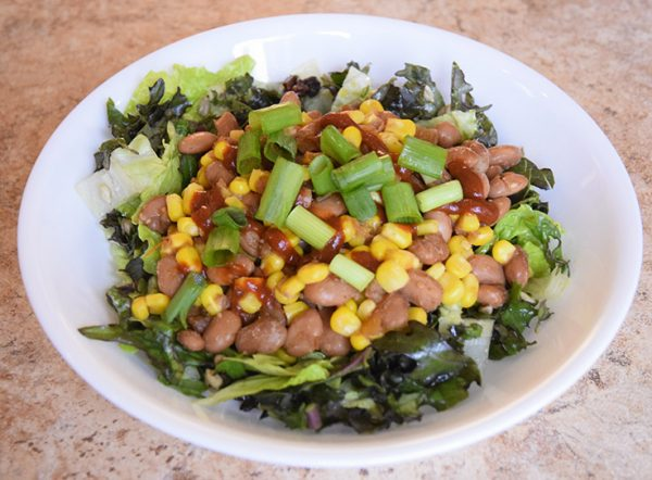 Spicy Sombrero Salad with warm beans and corn, kale, green onions, raisins, and salsa