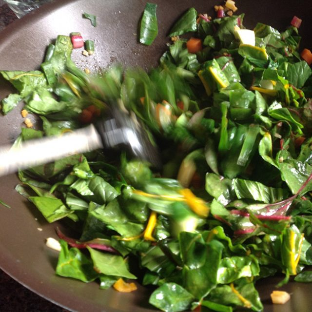 stir-frying greens in a wok