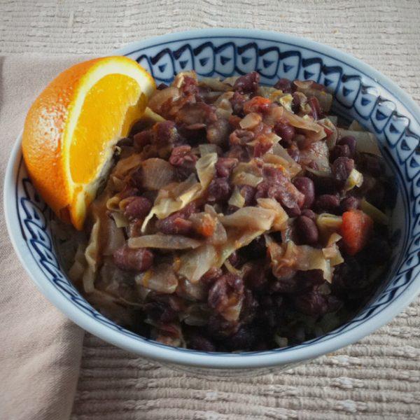 adzuki beans in orange sauce with a fresh orange wedge