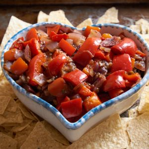 Bell peppers, onions, and mushrooms in a heart-shaped bowl with corn chips