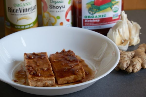 slabs of tofu marinating in barbecue sauce